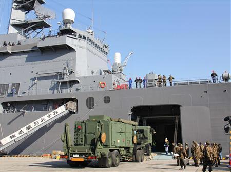 A lorry carrying a unit of the Patriot Advanced Capability-3 (PAC-3) missiles is loaded onto Japan's Maritime Self-Defense Force's (MSDF) transport vessel Osumi at an MSDF base in Kure, Hiroshima Prefecture, in this photo taken by Kyodo December 3, 2012. Japan expedited deploying the PAC-3 missile interceptors in Okinawa Prefecture to prepare for North Korea's planned rocket launch, Kyodo news reported. Mandatory Credit REUTERS/Kyodo