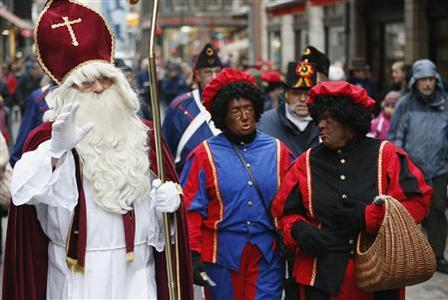 Saint Nicholas (L) is followed by his two assistants called 'Zwarte Piet' (Black Pete) during a traditional parade in central Brussels December 1, 2012. REUTERS-Francois Lenoir