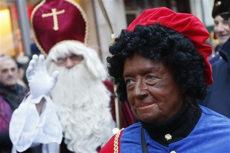 Saint Nicholas (L) waves next to one of his assistants called 'Zwarte Piet' (Black Pete) during a traditional parade in central Brussels December 1, 2012. REUTERS-Francois Lenoir