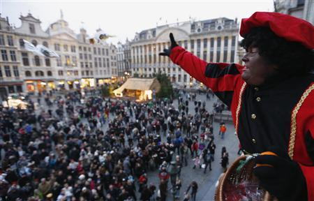 A woman dressed as 'Zwarte Piet' (Black Pete), the helper of Saint Nicholas, throws candy from the balcony of the City Hall at Brussels' Grand Place December 1, 2012. REUTERS-Francois Lenoir