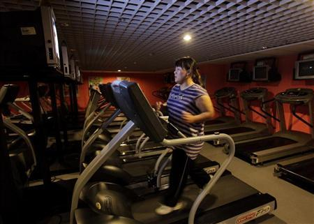 A woman runs on a treadmill as part of her training during a six-week programme in an exercise room at the Bodyworks weight loss campus in Beijing August 26, 2011. REUTERS/Soo Hoo Zheyang