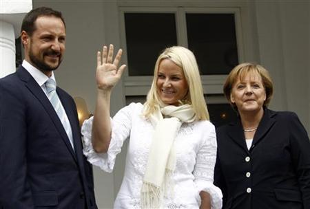 Norway's Crown Princess Mette-Marit (C) waves to people as Crown Prince Haakon (L) and German Chancellor Angela Merkel look on after they arrived at the island of Ruegen before their lunch in the town of Binz June 12, 2010. REUTERS/Fabrizio Bensch/Files