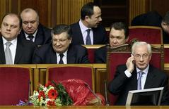 Then Ukrainian Prime Minister Mykola Azarov (R, front) talks on the phone after he was appointed as prime minister in Kiev in this March 11, 2010 file photo. REUTERS/Konstantin Chernichkin/Files