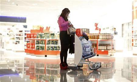 A woman from China stands with a shopping trolley in front of a Duty Free store at the Fraport airport in Frankfurt November 14, 2012. REUTERS/Lisi Niesner