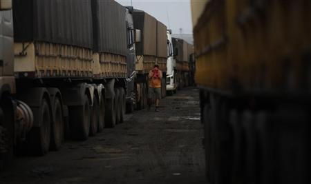 A Brazilian truck driver wipes his face with a towel after waking up as he waits to unload his freight of cereal grain at the rail terminal of America Latina Logistica (ALL) near highway BR-364 in Alto de Araguaia, Mato Grosso state, September 25, 2012. REUTERS/Nacho Doce