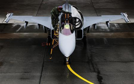 A pilot climbs out of a Swedish Saab Gripen F fighter jet during a media presentation at the Swiss Army Airbase in Emmen, central Switzerland October 12, 2012. REUTERS/Michael Buholzer