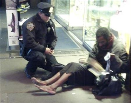 New York police officer Larry DePrimo gives a homeless man a pair of boots and socks in Times Square in this November 14, 2012 handout photo courtesy of Jennifer Foster. The photograph has drawn a deluge of praise after it was published on the police department's Facebook page this week. REUTERS/Jennifer Foster/Handout
