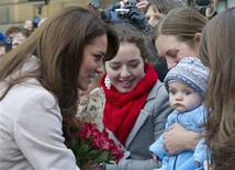 Britain's Catherine, Duchess of Cambridge is seen meeting James William Davies, the five month old son of Tessa Davies (R) who was named after Prince William, following a visit to the Guildhall in Cambridge, central England in this November 28, 2012 file photograph. REUTERS/Arthur Edwards/Pool/Files