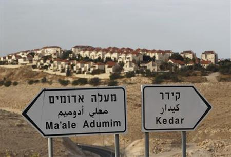 The West Bank Jewish settlement of Maale Adumim, near Jerusalem, is seen behind sign posts December 3, 2012. REUTERS/Ammar Awad