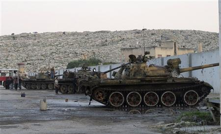 Free Syrian Army fighters gather around tanks which they say was captured from the Syrian army loyal to President Bashar al-Assad, at a base in Bab al-Hawa, near the Syrian-Turkish border November 28, 2012. Picture taken Novemver 28, 2012. REUTERS/Abdalghne Karoof