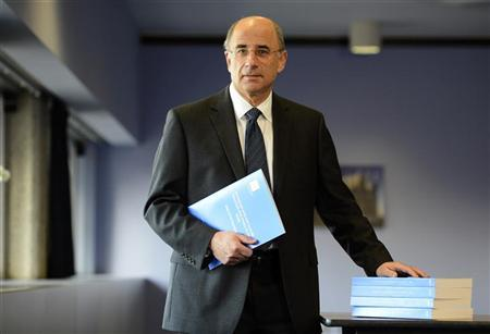 Lord Justice Brian Leveson poses with an executive summary of his report following an inquiry into media practices in central London November 29, 2012. REUTERS/Paul Hackett