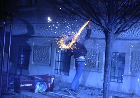 A protester throws fireworks during clashes in Maribor December 3, 2012. Protesters clashed with police in Slovenia's second largest city Maribor on Monday in a demonstration against budget cuts in the financially troubled Alpine state. Police said more than 20 people were arrested in Maribor and at least one policeman was injured after some from a crowd of around 6,000 protesters threw firecrackers, fireworks and rocks. REUTERS/Srdjan Zivulovic