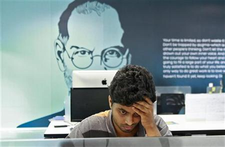 An employee works on a computer terminal against the backdrop of a picture of late Apple co-founder Steve Jobs at the Start-up Village in Kinfra High Tech Park in Kochi October 13, 2012.REUTERS/Sivaram