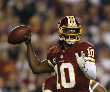 Washington Redskins quarterback Robert Griffin III throws against the New York Giants defense during the first half of their NFL football game in Landover, Maryland December 3, 2012. REUTERS/Gary Cameron