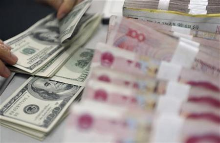 A clerk counts U.S. dollar banknotes after counting Chinese 100 Yuan banknotes at a branch of the Agricultural Bank of China in Qionghai, China's southmost Hainan province, November 12, 2012. REUTERS/China Daily CHINA OUT. NO COMMERCIAL OR EDITORIAL SALES IN CHINA