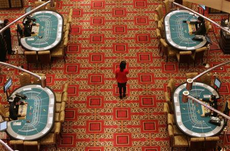 An employee walks past tables at SJM's flagship casino Grand Lisboa, owned by Macau tycoon Stanley Ho, before the opening ceremony in Macau in this February 11, 2007 file photo. REUTERS/Paul Yeung/Files