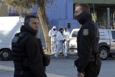 Greek police explosives experts work outside the local offices of the ultra-right Golden Dawn party after a bomb blast at Aspropyrgos suburb west of Athens December 4, 2012. The explosion occurred at the local offices of the party in the Athenian suburb early on Tuesday causing damage but no casualties, a police source said. REUTERS/Yorgos Karahalis