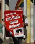 "An unidentified man removes placards of the far right National Democratic Party of Germany (NPD) from an office of the banned right-wing extremist group ""Nationaler Widerstand Dortmund"" (National Resistance Dortmund) in Dortmund August 23, 2012. REUTERS/Ina Fassbender (GERMANY - Tags: CRIME LAW POLITICS)"