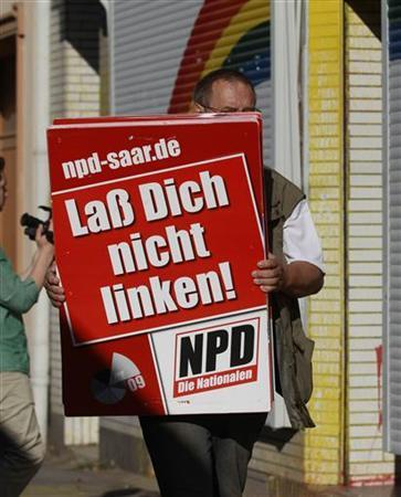 An unidentified man removes placards of the far right National Democratic Party of Germany (NPD) from an office of the banned right-wing extremist group ''Nationaler Widerstand Dortmund'' (National Resistance Dortmund) in Dortmund August 23, 2012. REUTERS/Ina Fassbender (GERMANY - Tags: CRIME LAW POLITICS)