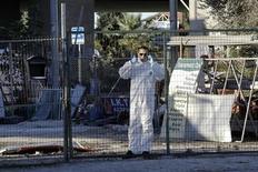 Una bomba artesanal estalló el martes en las oficinas del partido político Amanecer Dorado cerca de Atenas, derribando un muro y rompiendo las ventanas de un edificio cercano, pero sin causar heridos, dijo la policía. En la imagen, el parlamentario de Amanecer Dorado Ilias Kasidiaris, vestido con un uniforme protector, habla por teléfono junto a la zona donde se produjo la explosión en Aspropyrgos, Atenas, el 4 de diciembre de 2012. REUTERS/Yorgos Karahalis