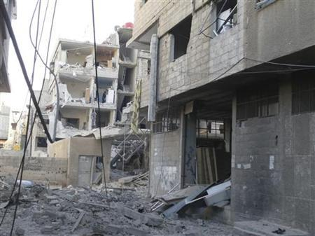 A man (C-L) checks his belonging at buildings damaged by what activists said were missiles fired by a Syrian Air Force fighter jet loyal to President Bashar al-Assad in the Akraba suburb of Damascus December 1, 2012. REUTERS/Thair Al-Damashqi/Shaam News Network/Handout