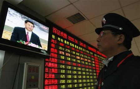 A security guard watches a screen showing newly-elected General Secretary of the Central Committee of the Communist Party of China (CPC) Xi Jinping speaking during a news conference, in front of an electronic board showing stock information at a brokerage house in Huaibei, Anhui province November 15, 2012. REUTERS/Stringer