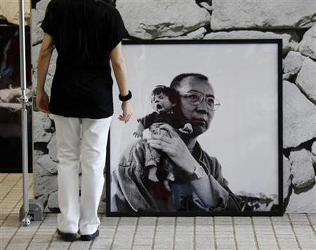 A visitor stands in front of a photograph of Nobel Laureate Liu Xiaobo carrying a puppet, taken by his wife Liu Xia, during her photo exhibition in Hong Kong June 9, 2012. REUTERS/Bobby Yip/Files