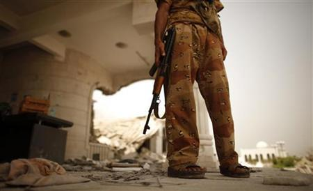 An army soldier stands guard outside a damaged government building in Zinjibar, the provincial capital of Yemen's southern province of Abyan, after the army retook it from al Qaeda-linked militants June 14, 2012. REUTERS/Khaled Abdullah/Files