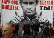 """People hold a banner, displaying an image of Russia's President Vladimir Putin, during the """"March of Millions"""" protest rally, held by opposition supporters, in St. Petersburg, September 15, 2012. REUTERS/Alexander Demianchuk"""