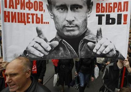 People hold a banner, displaying an image of Russia's President Vladimir Putin, during the ''March of Millions'' protest rally, held by opposition supporters, in St. Petersburg, September 15, 2012. REUTERS/Alexander Demianchuk