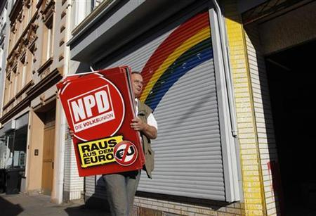 An unidentified man removes placards of the far right National Democratic Party of Germany (NPD) from an office of the banned right-wing extremist group ''Nationaler Widerstand Dortmund'' (National Resistance Dortmund) in Dortmund August 23, 2012. REUTERS/Ina Fassbender (GERMANY - Tags: POLITICS CRIME LAW)