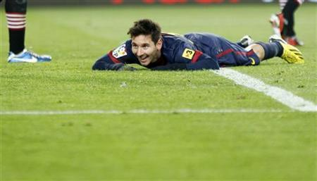 Barcelona's Lionel Messi smiles on the grass after missing a chance to score a third goal during their Spanish first division soccer match against Athletic Bilbao at Nou Camp stadium in Barcelona December 1, 2012. REUTERS/Gustau Nacarino