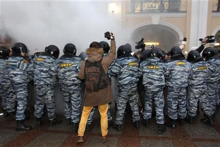 A photographer takes pictures of Interior Ministry officers during a protest rally to defend Article 31 of the Russian constitution, which guarantees the right of assembly, in St. Petersburg October 31, 2012. REUTERS/Alexander Demianchuk