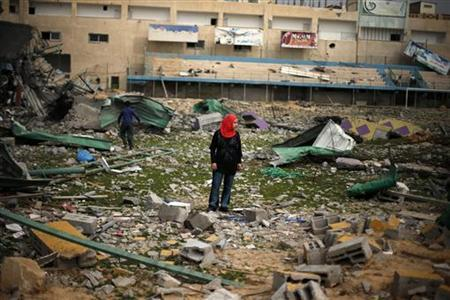 A Palestinian girl looks at a soccer stadium, which witnesses said was destroyed in an Israeli air strike during an eight-day conflict, in Gaza City December 4, 2012. REUTERS/Suhaib Salem