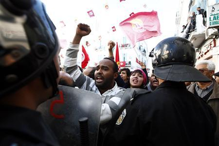 Members of main labour union body UGTT and pro-government Islamists clash near riot police during a gathering where UGTT members called for a general strike and downfall of the government led by the Islamist Ennahda party in Tunis December 4, 2012. REUTERS/Anis Mili