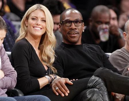 Actor Eddie Murphy (R) sits with Australian model Paige Butcher (L) courtside at the Staples Center during the NBA basketball game between the Los Angeles Lakers and Phoenix Suns in Los Angeles November 16, 2012. REUTERS/Danny Moloshok