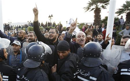 Pro-government Islamists clash near riot police during a demonstration against labour union UGTT that called for a general strike and downfall of the government led by the Islamist Ennahda party at Kasba in Tunis December 4, 2012. REUTERS/Zoubeir Souissi