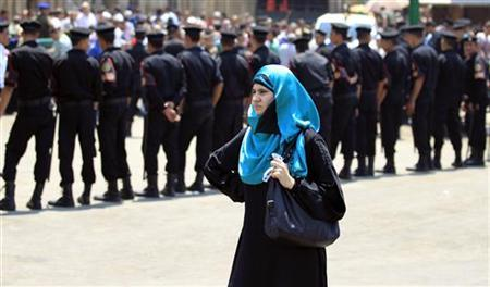 A woman waits as security personnel close off a street leading to Al-Azhar mosque when Egypt's President Mohamed Mursi is in it performing the Al-Gomaa prayer in Cairo August 17, 2012. REUTERS/Mohamed Abd El Ghany