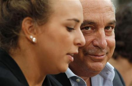 Retail billionaire Philip Green , whose Arcadia Group owns the Topshop clothing chain, sits with his daughter Chloe before the presentation of the Topman Design 2012 Spring/Summer collection during London Fashion Week September 21, 2011. REUTERS/Suzanne Plunkett