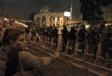 A woman stands near barbed wire in front of the presidential palace in Cairo, December 4, 2012. Egyptian police battled thousands of protesters outside President Mohamed Mursi's palace in Cairo on Tuesday, prompting the Islamist leader to leave the building, two presidential sources said. REUTERS/Mohamed Abd El Ghany