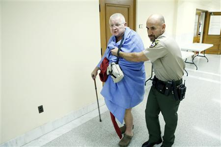 A San Francisco Sheriff's Deputy removes a nude protester who removed his clothes in the supervisors' legislative chambers in San Francisco City Hall, California, December 4, 2012. REUTERS/Beck Diefenbach