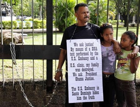 Miguel Familia, a dual citizen of the United States and the Dominican Republic, stands chained to the fence of the U.S. consulate with his daughters Ashley (C) and Salome (R), during a demonstration by him to make public his lawsuit against the U.S. government and a New Jersey laboratory that performed a DNA test on him in 2005, in Santo Domingo December 4, 2012. REUTERS/Ricardo Rojas