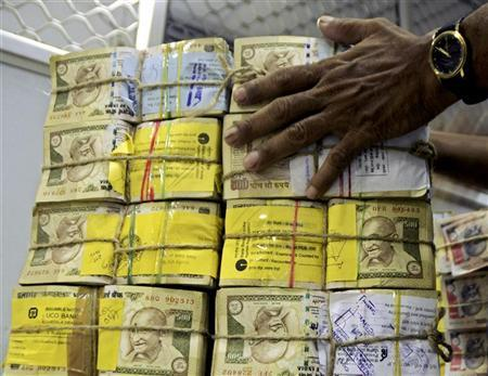 A bank employee counts bundles of Indian currency at a cash counter in Tripura, July 7, 2009. REUTERS/Jayanta Dey/Files