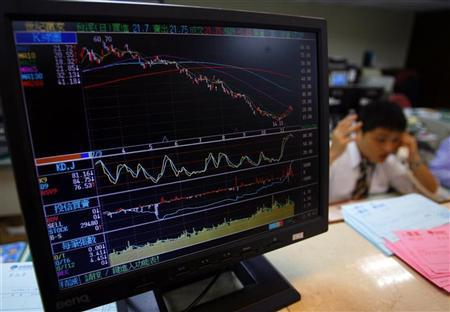 An employee works behind a monitor displaying stock information at a securities company in Taipei November 20, 2008. REUTERS/Nicky Loh/Files