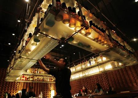 A bartender reaches out for a bottle at a bar in a luxury hotel in Mumbai November 22, 2008. REUTERS/Arko Datta/Files