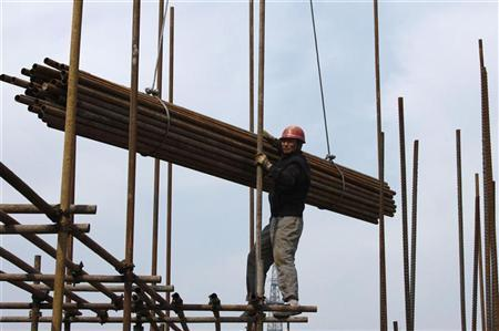 A worker stands on scaffolding at a construction site for a residential project in Huaibei, Anhui province April 8, 2010. REUTERS/Stringer/Files