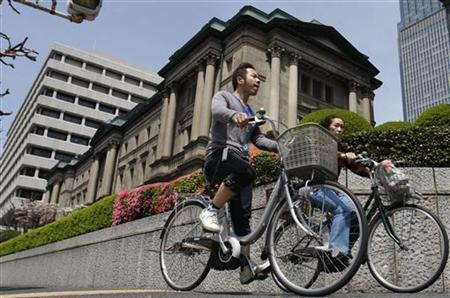 People ride bicycles past the Bank of Japan headquarters in Tokyo April 21, 2010. REUTERS/Yuriko Nakao
