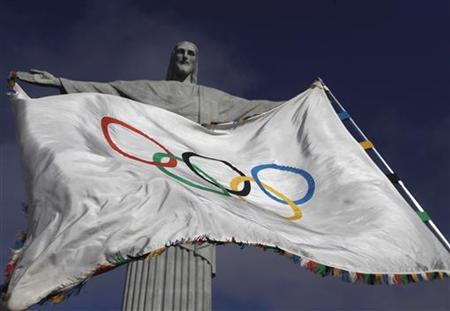 The Olympic Flag flies in front of ''Christ the Redeemer'' statue during a blessing ceremony in Rio de Janeiro August 19, 2012. REUTERS/Ricardo Moraes/Files