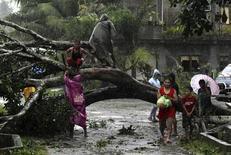 """Люди у поваленного тафуном """"Бофа"""" дерева в городе Тагум на юге Филиппин 4 декабря 2012 года. Около 230 человек погибли и сотни пропали без вести из-за схода селей и наводнений на Филиппинах, причиной которых стал сильнейший за год тайфун, сообщили власти островного государства. REUTERS/Stringer"""