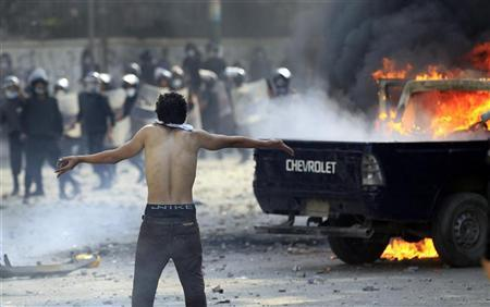 A protester stands in front of riot police as others set fire to police vehicles during clashes along a road which leads to the U.S. embassy, near Tahrir Square in Cairo September 13, 2012. REUTERS/Mohamed Abd El Ghany